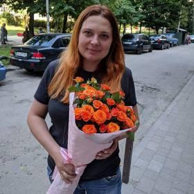 Девушка с букетом оранжевых кустовых роз - фото