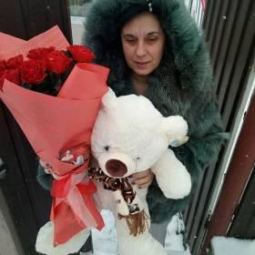 Получательница с букетом красных роз и мишкой - фото