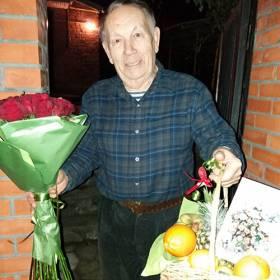 Именинник с букетом роз и корзиной фруктов - фото