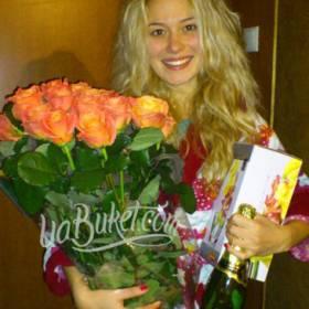 Девушка с букетом оранжевых роз, конфетами и шампанским - фото