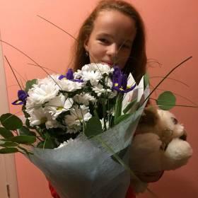 Девушка с букетом и цветов и игрушкой - фото