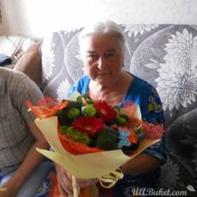 Бабушка с букетом в момент доставки