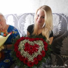 Девушка с композицией из роз в форме сердца