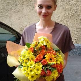 Милая девушка с букетом роз, хризантем и гербер