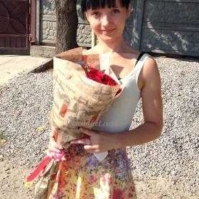 Девушка с букетом роз в бумажной упаковке - фото