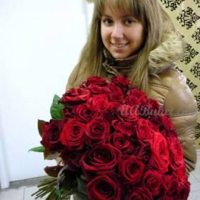 круглый букет красных роз в руках девушки - фото