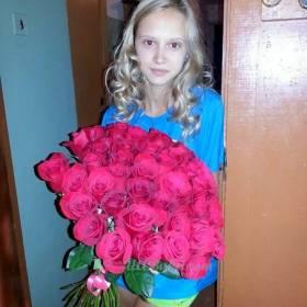 Девушка в дверях квартиры с букетом роз - фото