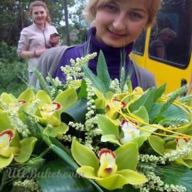 Девушка с букетом зеленых орхидей - фото