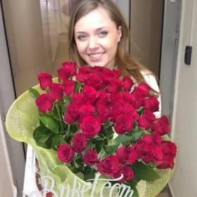 Счастливая девушка с букетом красных роз - фото